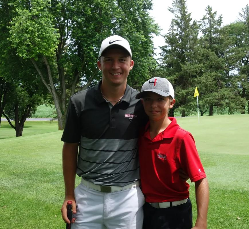 Two junior golfers pose for a picture